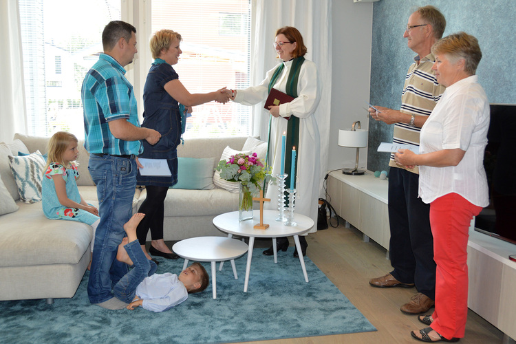 The blessing of a home. A priest and family members.