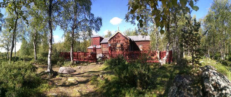 Punaruskea puukirkko luonnon keskellä.