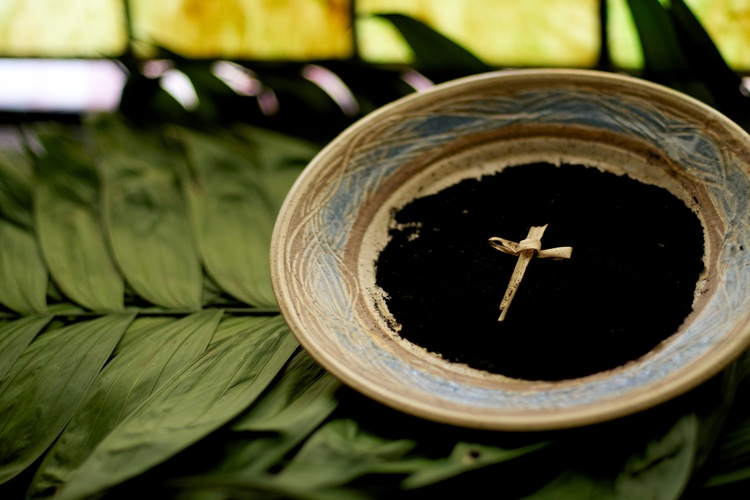 A cross on a plate containing ash.