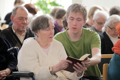 Young man assisting an old woman at church service.