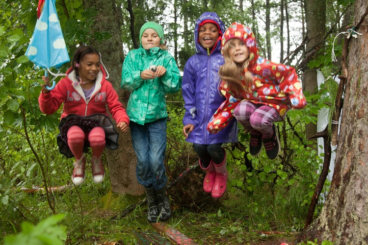 Children jumping in a rainy forest.