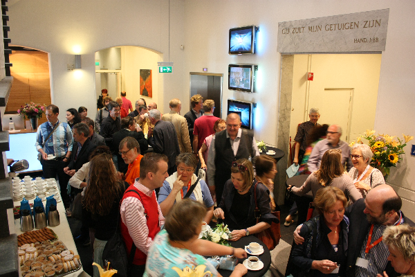 People stranding and drinking coffee in a hall.
