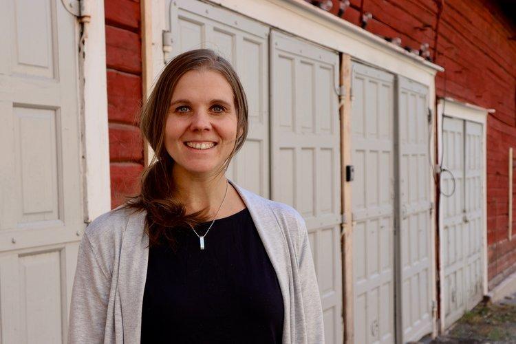 Amanda Audas-Kass porträtt mot en röd gammal träbyggnad