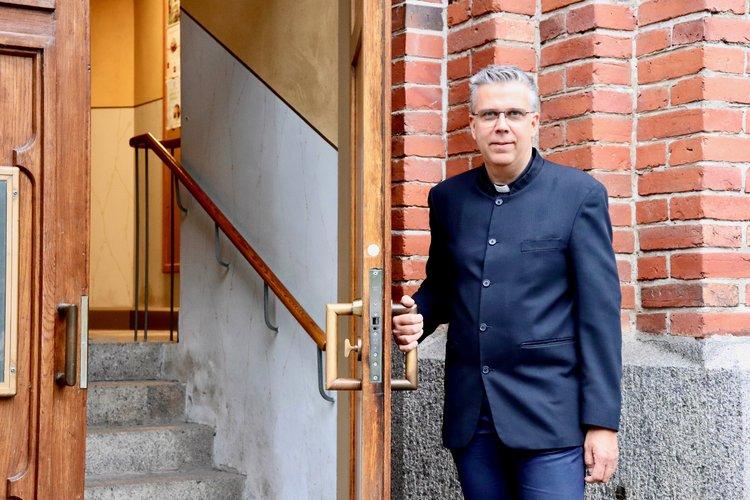 Kyrkoherde Mikael Forslund håller dörren till kyrkan öppen.