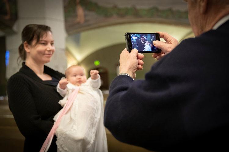 Morfar som tar foto av mamman och dopbabyn med mobiltelefon.
