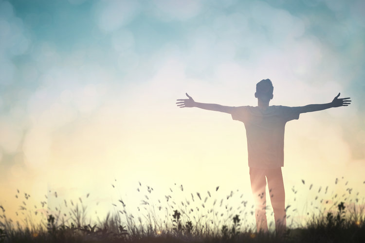 Frihet. Pojke står på äng i soluppgången med händerna utsträckta.