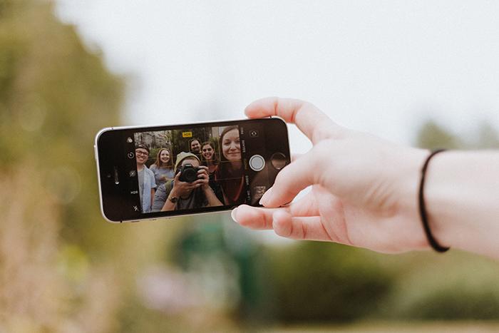 Smarttelefon på vars skärm man ser unga vuxna.