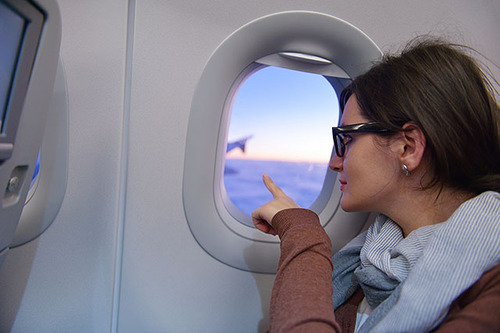 A woman looks out from the window of an airoplane.